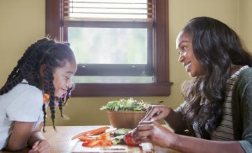 mother and daughter sit across dining room table from one another looking at vegetables