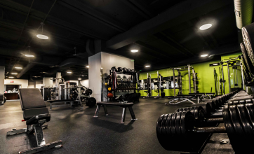 dark empty gyms with dumbbells, benches, and fitness machines