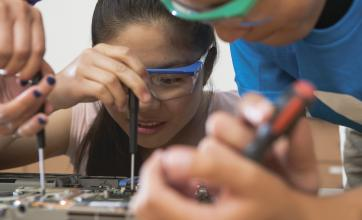 Adolescent kids wearing safety goggles using screwdrivers on a circuit board