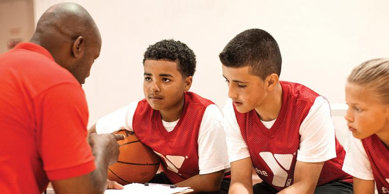 coach speaks to benched adolescent basketball players in red jersey